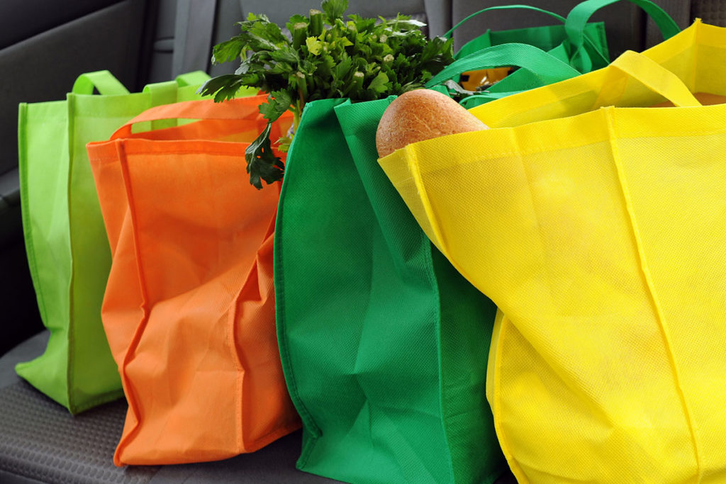 Four filled and colorful eco-friendly shopping bags in the back seat of a car
