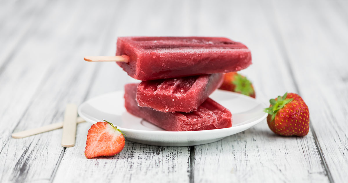 Old wooden table with homemade Strawberry Popsicles