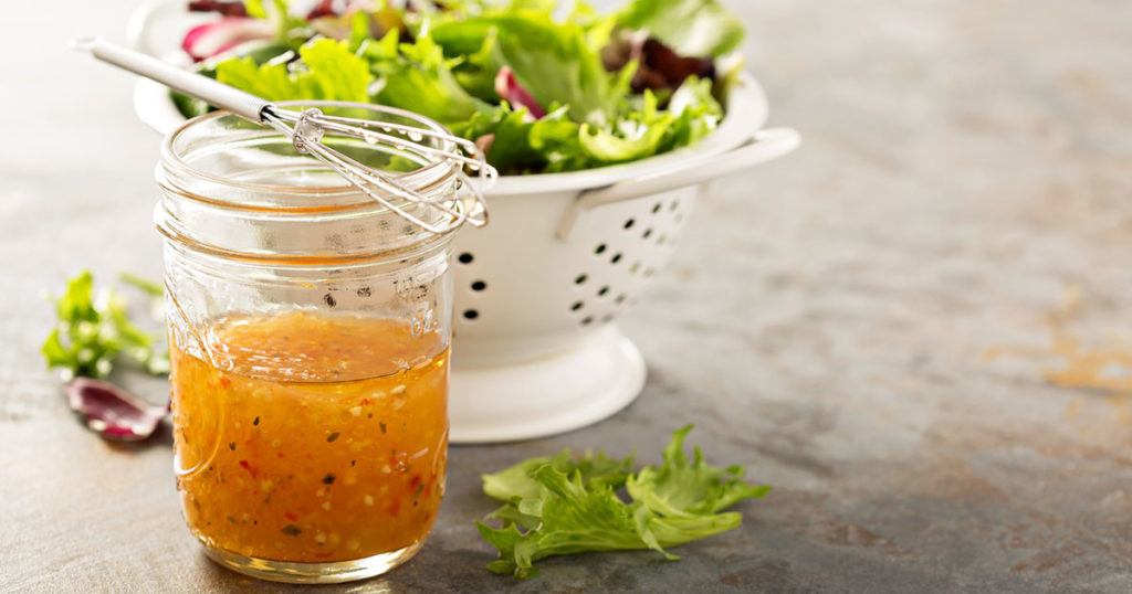 vinaigrette dressing in a mason jar with fresh vegetables on the table