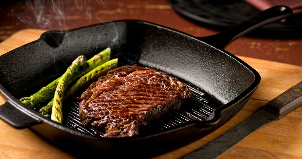 steak with asparagus in hot cast iron skillet
