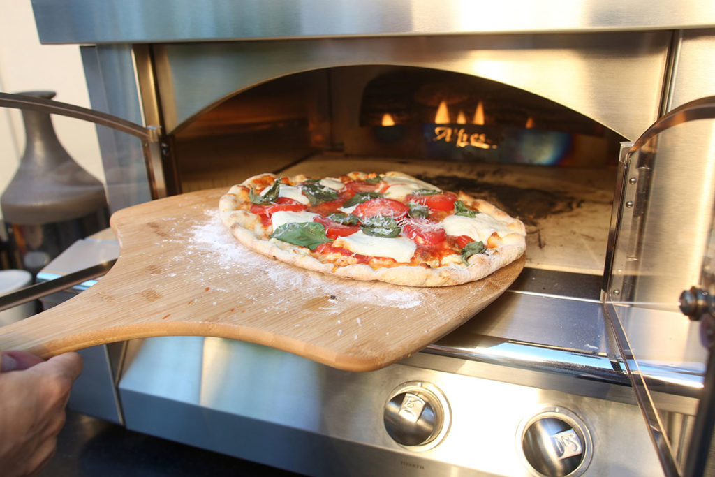 Placing a pizza on a wooden board into Alfresco pizza oven